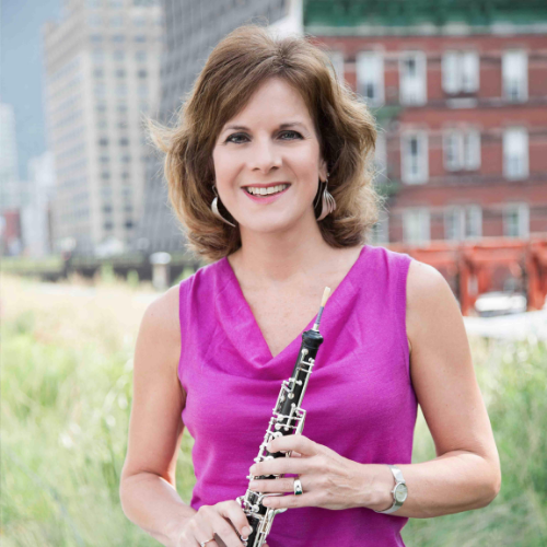 Nancy Ambrose King wears a magenta blouse and smiles at the camera as she holds her oboe.