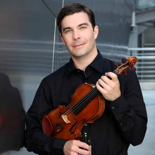 Nathan Cole holds a violin and looks into the camera
