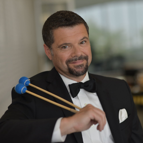 Pablo Rieppi in a tuxedo holding mallets smiling at the camera.