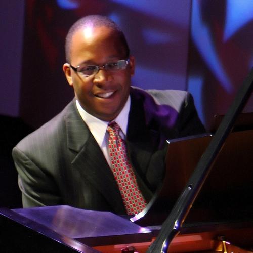 Howard Watkins sits behind a piano and smiles at the camera.