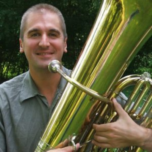 Eric Bubacz smiles at the camera and holds his tuba.