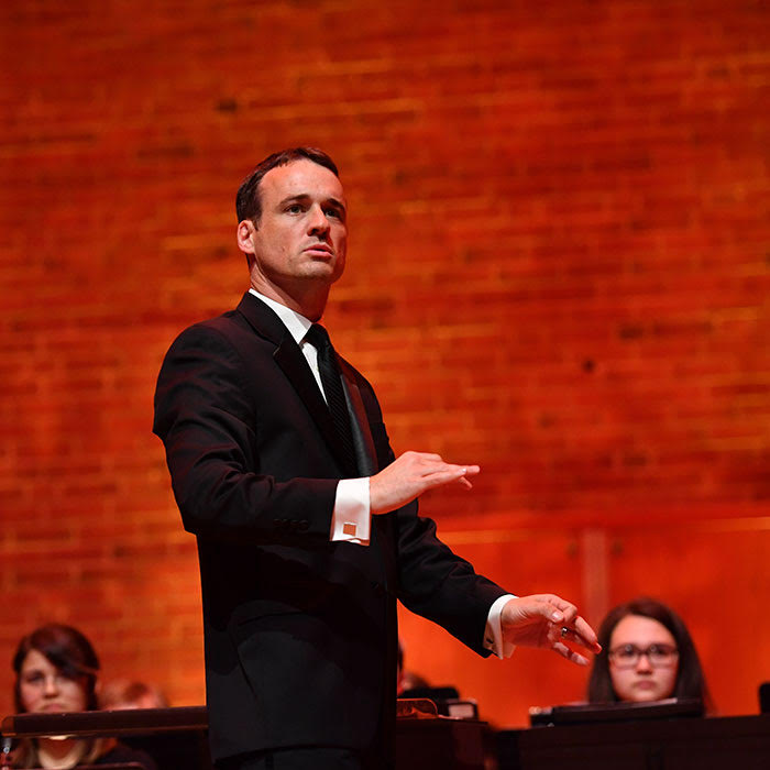 Christopher Cicconi conducts an ensemble in front of a red brick background.
