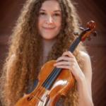 Alayna Nicotera holds her violin and smiles to the camera.