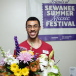 Brennen Braden stands in front of an SSMF banner and smiles from behind a bouquet of flowers.
