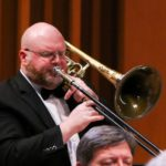 Bruce Mangan wears a tuxedo and plays his trombone in front of a red