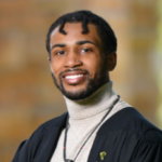 Cameron Noel wears a turtleneck and academic gown and smiles at the camera.