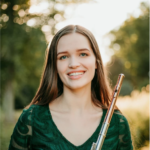 Katie Grischow wears green and smiles at the camera holding her flute.